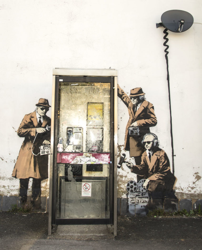 Banksy street art beside a call box in Cheltenham